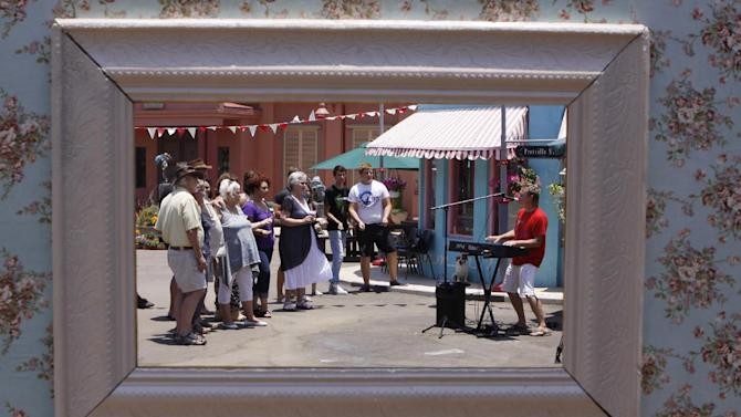 """In this photo taken Thursday, Jan. 10, 2013 visitors to the film set of the Afrikaans musical film """"Pretville"""" take part in a sing-a-long, in Hartebeespoort, South Africa. The movie indulges in rock'n roll, vintage cars, greasers in sneakers, pin curl hairstyles and swing dresses, lots of pastel pink and blue, and double-thick strawberry milkshakes with extra cream. (AP Photo/Denis Farrell)"""
