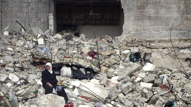 In this Thursday, Feb. 6, 2013 photo, a Syrian woman sits on the ruins of her house, which was destroyed in an airstrike by government warplanes a few days earlier, killing 11 members of her family, in the neighborhood of Ansari, Aleppo, Syria. (AP Photo/Abdullah al-Yassin)