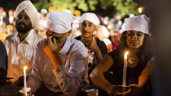 People cover their heads at a candle light vigil in Oak Creek, Wis., Tuesday Aug. 7, 2012,  for the victims of a mass shooting at the Sikh Temple of Wisconsin on Sunday. The vigil was held during the national night out event at the Oak Creek Civic Center.  (AP Photo/Tom Lynn)