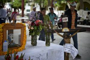 Students walk past an altar in memory of killed and …