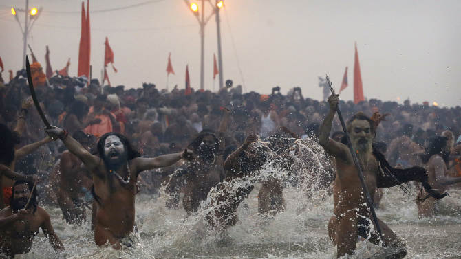 Indian Hindu holy men, or Naga Sadhus, run naked into the water at Sangam, the confluence of the Ganges, Yamuna and mythical Saraswati river, during the royal bath on Makar Sankranti at the start of the Maha Kumbh Mela in Allahabad, India, Monday, Jan. 14, 2013. Millions of Hindu pilgrims are expected to take part in the large religious congregation that lasts more than 50 days on the banks of Sangam which falls every 12 years. (AP Photo/Kevin Frayer)