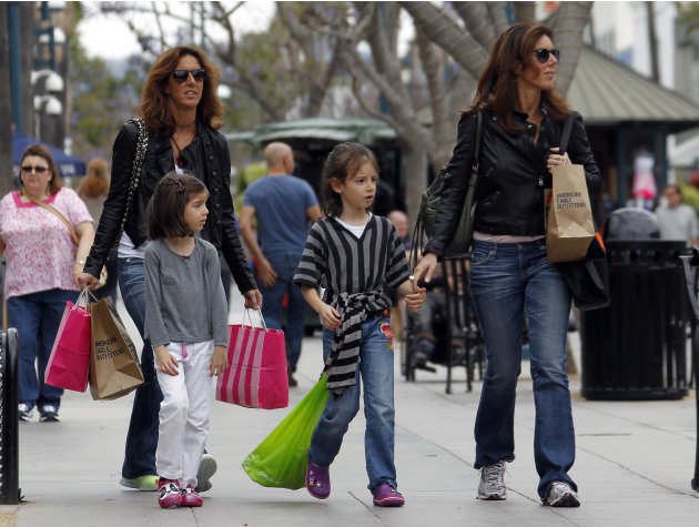In this April 24, 2012, file photo, women and girls carry purchases on the Third Street Promenade in Santa Monica, Calif. The Commerce Department said Friday, April 27, 2012, that the economy expanded