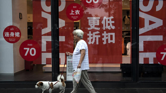 A Chinese woman carries a dog walks past a fashion boutique having a sale at a shopping mall in Beijing, China Monday, July 15, 2013. China's leaders face new pressure to stimulate a slowing economy after growth fell to its lowest since 1991, hurt by weak trade and efforts to cool a credit boom. (AP Photo/Andy Wong)