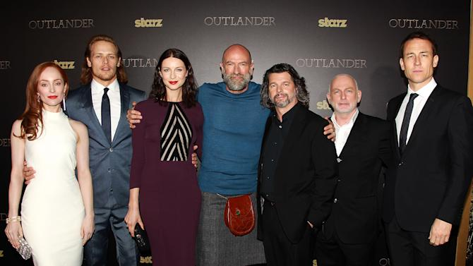 """In this image released by Starpix, Lotte Verbeek, from left, Sam Heughan, Caitriona Balfe, Graham McTavish, Ronald D. Moore, Gary Lewis  and Tobias Menzies pose at the mid-season screening of the original series """"Outlander,"""" at the Ziegfeld Theatre on Wednesday, April 1, 2015, in New York. The series continues on Sunday, April 4 on Starz. (AP Photo/Starpix, Dave Allocca)"""