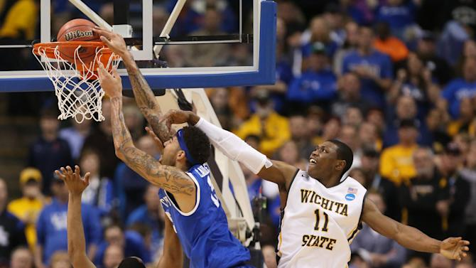 Kentucky forward Willie Cauley-Stein is fouled by Wichita State forward Darius Carter as he dunks the ball in first half action during a Third Round NCAA Tournament game between Wichita State and Kentucky on Sunday, March 23, 2014, at the Scottrade Center in St. Louis. Also defending on the play is Wichita State forward Cleanthony Early, right. (AP Photo/ St. Louis Post-Dispatch, Chris Lee)