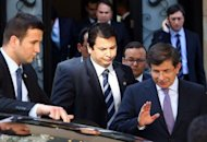 Turkey's Foreign Minister Ahmet Davutoglu (R) leaves a meeting focused on Syria with army generals and other officials in Ankara