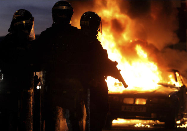 Riot police stand next to a burned out car after Loyalist protesters attacked police lines, in east BelfastNorthern Ireland, Saturday Jan. 12, 2013. Police used water cannons as four officers were inj