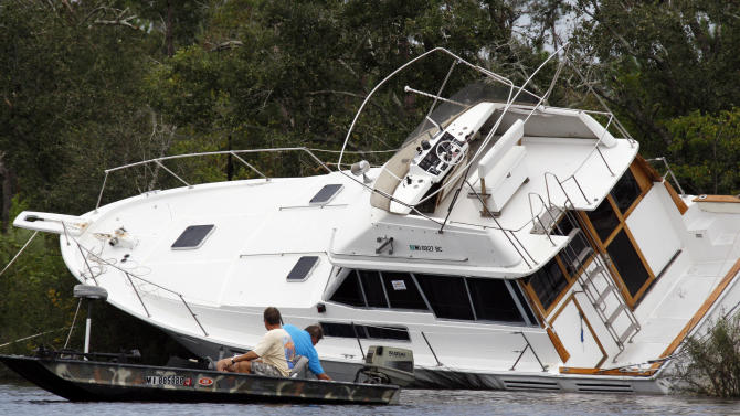 Several men try to free this grounded yacht on Twin Lake, near Diamondhead, Miss., Friday, Aug. 31, 2012. Area residents often anchor their boats during storms in lake. Strong winds and high waters caused by Isaac forced the grounding. A house boat was demolished nearby.  (AP Photo/Rogelio V. Solis)