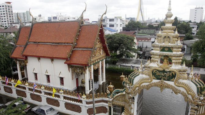 A Thai Buddhist monk stands on sandbags at the flooded Amarakire temple in Bangkok, Thailand, Saturday, Oct. 29, 2011. The complex network of flood defenses erected to shield Thailand's capital from the country's worst floods in nearly 60 years was put to the test Saturday as coastal high tides hit their peak. (AP Photo/Sakchai Lalit)