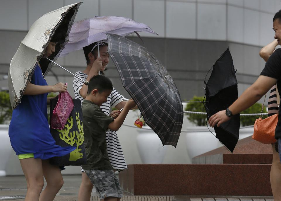 Tourists battle against strong wind near the waterfront in Hong Kong Wednesday, Aug. 14, 2013. Typhoon Utor lashed Hong Kong with wind and rain, closing down the bustling Asian financial center Wednesday before sweeping toward mainland China. (AP Photo/Vincent Yu)