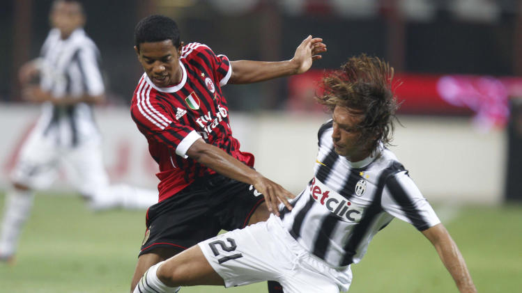 Juventus midfielder Andrea Pirlo, right, challenges for the ball with AC Milan midfielder Urby Emanuelson, of Netherlands, during a pre-season  'Berlusconi Trophy' soccer match at the San Siro stadium in Milan, Italy, Sunday, Aug. 21, 2011. (AP Photo/Luca Bruno)