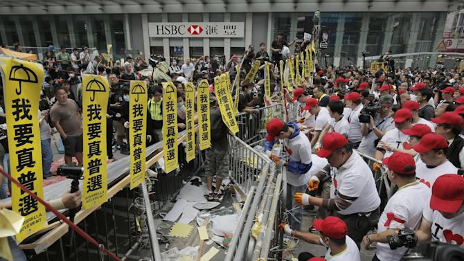 "People wearing ""I love Hong Kong"" T-shirts and red baseball caps help dismantle the first row of barricades as police start enforcing the court-ordered clearance of a protest area in Mong Kok district of Hong Kong Wednesday, Nov. 26, 2014. Hong Kong authorities cleared street barricades from a pro-democracy protest camp in the volatile Mong Kok district for a second day Wednesday after a night of clashes in which police arrested 116 people. Yellow signs say, ""I want genuine universal suffrage"". (AP Photo/Vincent Yu)"