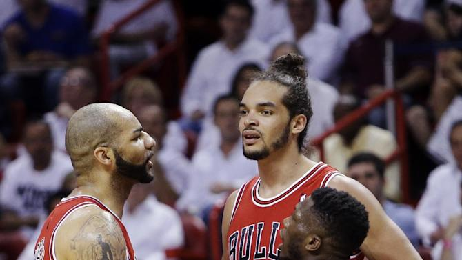 Chicago Bulls forward Carlos Boozer, left, center Joakim Noah, center, and guard Nate Robinson (2) huddle during the first half of Game 2 of their NBA basketball playoff series in the Eastern Conference semifinals against the Miami Heat, Wednesday, May 8, 2013, in Miami. (AP Photo/Lynne Sladky)
