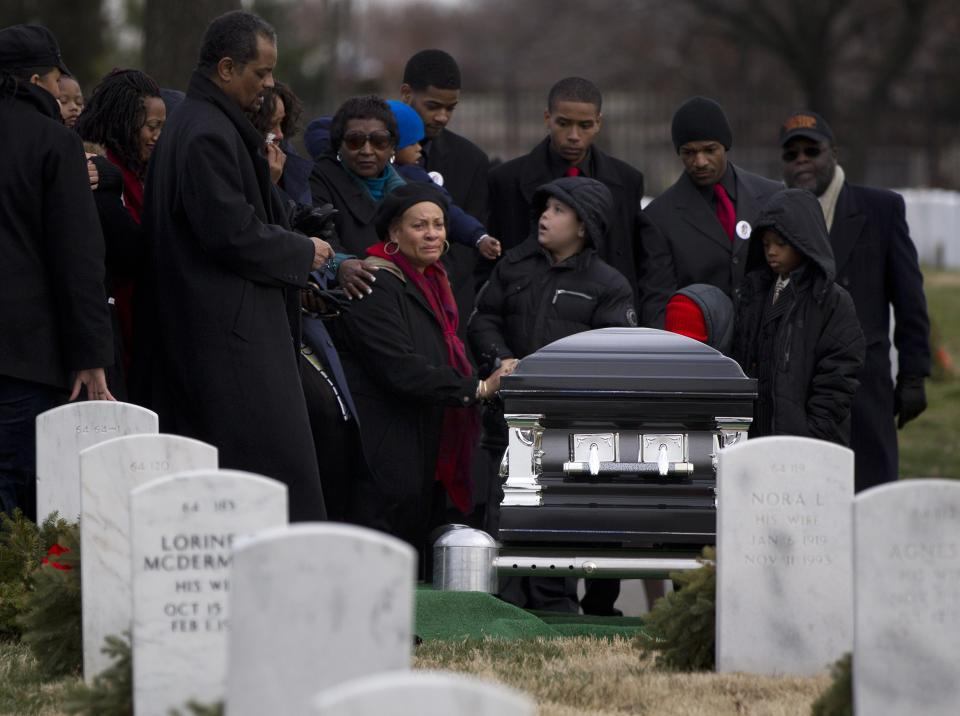 Friends and family of former Tuskegee airman, retired Lt. Col. Luke Weathers, gather around his casket during burial services at Arlington National Cemetery in Arlington, Va.,  Friday, Jan. 20, 2012.  (AP Photo/Evan Vucci)