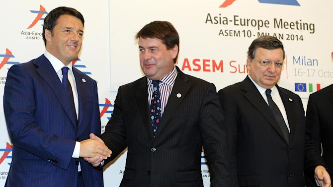 Slovakian Foreign Minister Miroslav Lajcak (center) is welcomed by Italian Priemier Matteo Renzi (left) and EU Commission President Jose Manuel Barroso, at the 10th Asia-Europe Meeting (ASEM) in Milan, Italy, Thursday, Oct. 16, 2014. (AP Photo/Daniel Dal Zennaro, Pool)