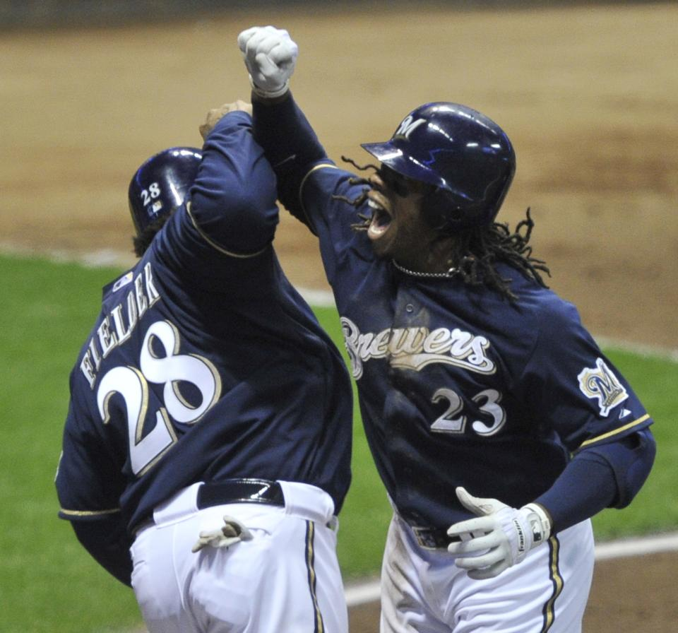 Milwaukee Brewers' Rickie Weeks (23) is congratulated by Prince Fielder (28) after Weeks hit a two-run home run during the fourth inning of Game 2 of baseball's National League championship series against the St. Louis Cardinals Monday, Oct. 10, 2011, in Milwaukee. (AP Photo/Jim Prisching)