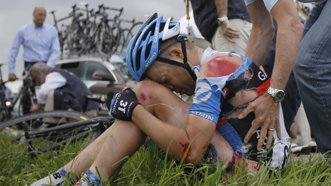 Injured Thomas Danielson of the US sits in the grass after a crash in thew pack at some 20 kilometers from he finish line during the sixth stage of the Tour de France cycling race over 207.5 kilometers (129 miles) with start in Epernay and finish in Metz, France, Friday July 6, 2012. (AP Photo/Laurent Cipriani)