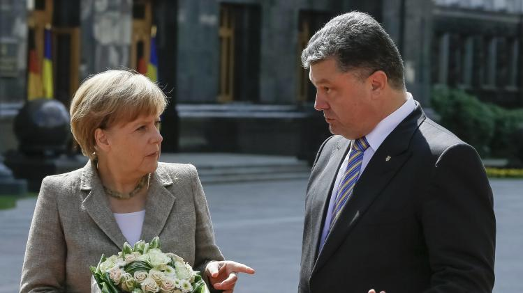 Merkel and Poroshenko gesture while they meet in Kiev