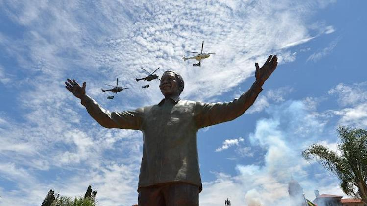 Helicopters carrying the South African flag fly over a 9-meter bronze statue of Nelson Mandela which was unveiled on December 16, 2013 in Pretoria