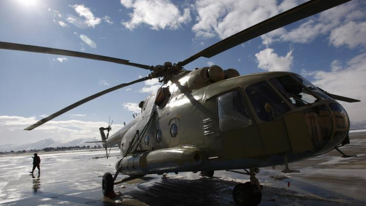 An Afghan soldier walks next to a refurbished Mi-17 helicopter at the military airport in Kabul