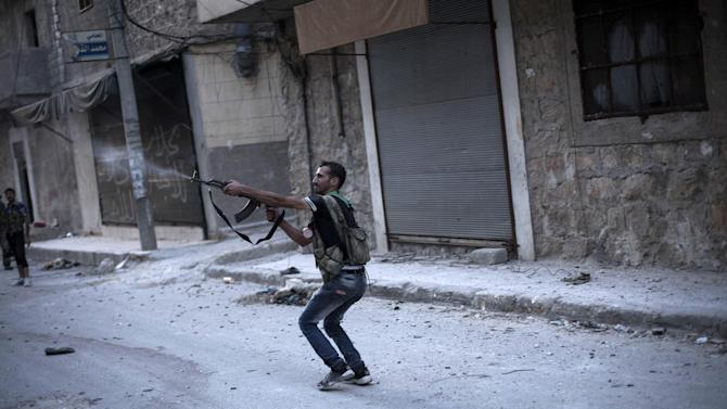 In this Wednesday, Sept. 19, 2012 photo, a Free Syrian Army fighter fires his weapon against Syrian Army positions in the Amariya district in Aleppo, Syria. (AP Photo/Manu Brabo)