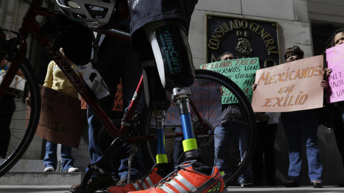 Cyclist Carlos Gutierrez, a double amputee, center, stands with his bike during a stop at the Mexican Consulate, Thursday, Nov. 7, 2013, in San Antonio. Gutierrez, a Mexican asylum seeker who fled to the U.S. after extortionists cut his legs off for not paying the extortion fees, is riding his bike from El Paso, Texas to Austin, Texas, to raise awareness on the situation of political asylum seekers. (AP Photo/Eric Gay)