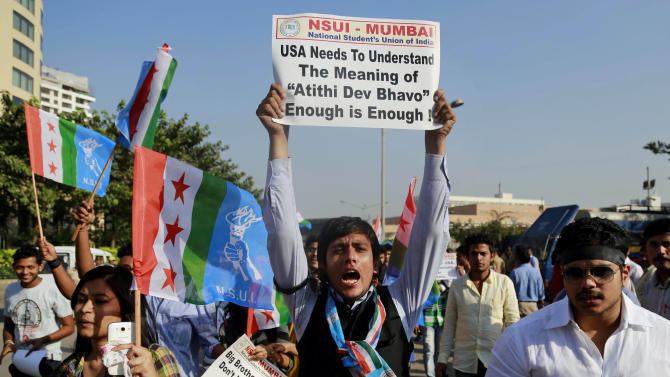"A member of the National Students Union of India (NSUI), the student wing of India's ruling Congress party, shouts slogans during a protest outside the U.S. consulate in Mumbai, India, Friday, Dec. 20, 2013. India's Information Minister Manish Tewari lashed out at the United States on Friday and demanded an apology for the treatment and arrest of Devyani Khobragade, India's deputy consul general in New York, saying America cannot behave ""atrociously"" and get away with it. Meaning of ""Atithi Dev Bhavo"" on placard is ""Guest is God"". (AP Photo/Rafiq Maqbool)"