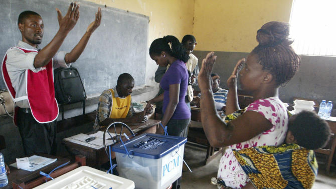 A woman, right, holding her baby, displays her hands to an election official, left, to show that she has not previously voted, during municipal elections held in the city of Maputo, Mozambique, Wednesday, Nov. 20, 2013. Mozambicans are voting in municipals elections amid tension and sporadic violence between the government and the main opposition group, which says it is boycotting the election. State radio said voting was proceeding peacefully on Wednesday, a day after the opposition Renamo group said it had no intention of disrupting the vote. (AP Photo/Ferhat Momade)