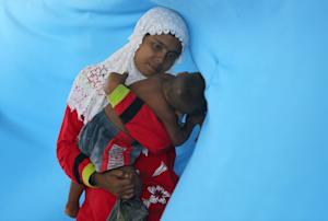 A migrant mother carries her child at a temporary shelter…