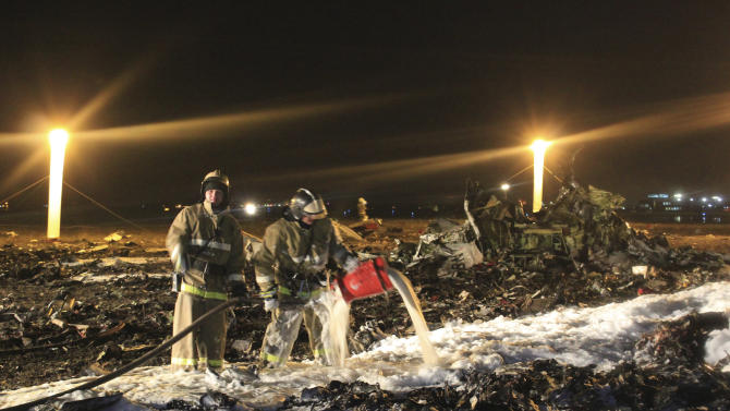 FILE - In this Nov. 17, 2013, file photo provided by Russian Emergency Situations Ministry, firefighters and rescuers work at the crash site of a Russian passenger airliner near Kazan, the capital of the Tatarstan republic, about 720 kilometers (450 miles) east of Moscow. On Friday, Dec. 6, 2013, an investigator said there were reasons to believe the pilot who sent the Boeing 737 into a near-vertical dive, killing all 50 on board, had received his license illegally in a small training center that is no longer functioning. (AP Photo/Russian Emergency Situations Ministry, file)