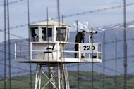 A UN peacekeeper is seen on an observation tower in the largely abandoned city of Quneitra, in the demilitarized United Nations Disengagement Observer Force (UNDOF) zone, in the Golan Heights, on March 8, 2013. A group of 21 UN peacekeepers seized by Syrian rebels on the Golan were still being held on Saturday after a two-hour truce during which their release had been expected, a watchdog said