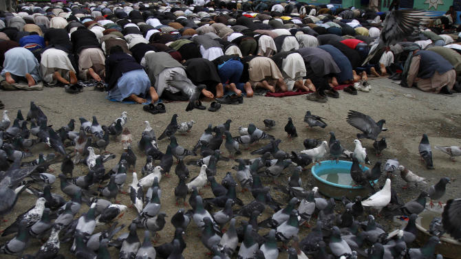 Pigeons surround Afghan men kneeling down for Friday payers near the Pul-e Khishti mosque in Kabul, Afghanistan, Friday, April 12, 2013. Taliban militants attacked an Afghan army outpost near the eastern border with Pakistan on Friday, killing over a dozen Afghan National Army soldiers, the Defense Ministry said.(AP Photo/Ahmad Jamshid)