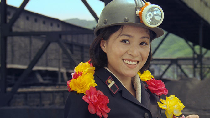 "FILE - In this file image made out of film ""Comrade Kim Goes Flying"" released on Oct. 3, 2012 by Busan International Film Festival, Comrade Kim Yong Mi played by Han Jong Sim smiles as she wears a coal miner's helmet. North Korea's progress in filmmaking technology has been slow, especially when compared to a South Korean film industry that's the envy of Asia. The country's relative isolation means North Korean filmmakers rarely get the opportunity to work with foreign artists. A notable exception was ""Comrade Kim goes Flying,"" a romantic comedy from 2012 about a young female coal miner who dreams of becoming a trapeze artist. The movie was co-produced with Western partners. (AP Photo/Busan International Film Festival, File)"