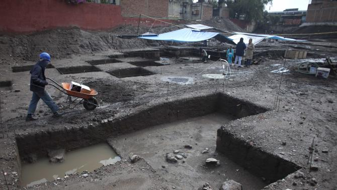 A worker pushes a wheelbarrow through a recently discovered archeological site in Mexico City, Friday, July 13, 2012. According to Mexico's National Institute of Anthropology and History, INAH, the site is about 700 years old and is a neighborhood of the Tepaneca merchants. (AP Photo/Alexandre Meneghini)