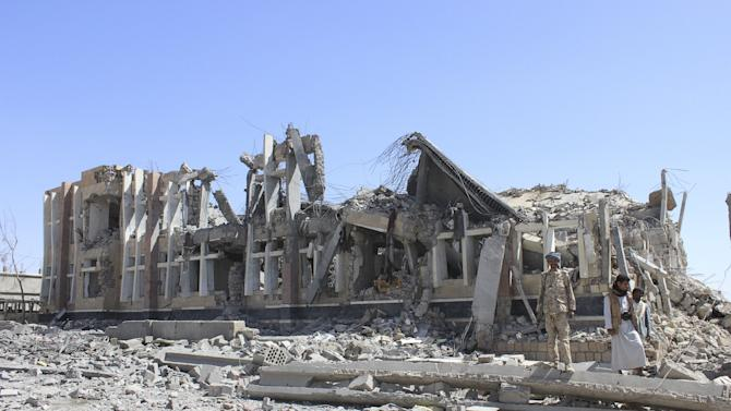 Houthi militants stand near a government building destroyed by a Saudi-led air strike in Yemen's northwestern city of Saada