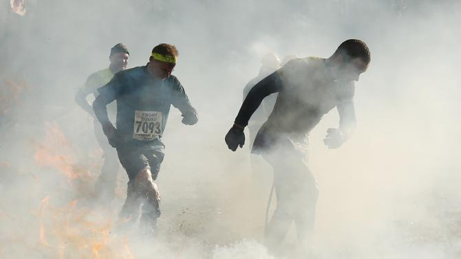 Competitors run through smoke and fire during the Tough Guy event in Perton