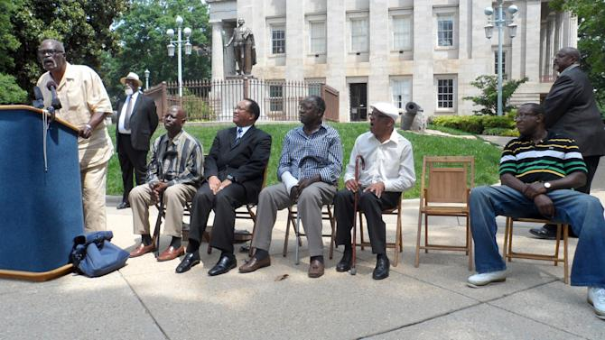 Connie Tindall, a member of the Wilmington Ten, speaks at a news conference outside the State Capitol building in Raleigh in which the group called on Gov. Beverly Perdue to pardon them, in this May 2012 photo. Sitting (from left to right) are Wilmington Ten members Willie Earl Vereen; Benjamin Chavis Jr.; James McKoy; Marvin Patrick; and Willie Moore, the brother of late Wilmington 10 member Wayne Moore. Outgoing North Carolina Gov. Beverly Perdue issued pardons Monday, Dec, 31, 2012 to the Wilmington 10, a group wrongly convicted 40 years ago in a notorious Civil Rights-era prosecution that led to accusations of the state holding political prisoners. (AP Photo/Wilmington Star-News, Patrick Gannon)