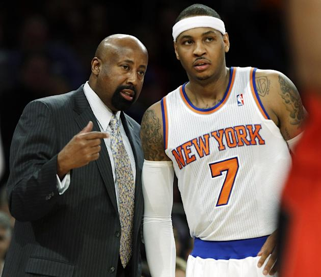 New York Knicks head coach Mike Woodson talks to Carmelo Anthony, right, during the first half of an NBA basketball game against the Toronto Raptors, Wednesday, Feb. 13, 2013, in New York. (AP Photo/F