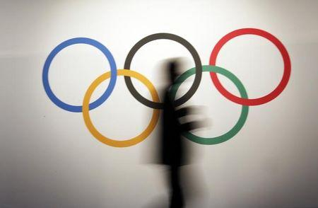 A man walks past the Olympic rings before the opening of the 127th International Olympic Committee session in Monaco