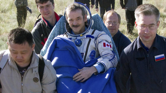 Ground personnel carry Canadian astronaut Chris Hadfield, center, after Russian Soyuz space capsule landed some 150 kilometers (94 miles) southeast of the town of Dzhezkazgan in central Kazakhstan, Tuesday, May 14, 2013.  Soyuz space capsule carrying a three-man crew including Hadfield,  returning from a five-month mission to the International Space Station landed safely Tuesday on the steppes of Kazakhstan. (AP Photo/ Sergei Remezov, Pool)