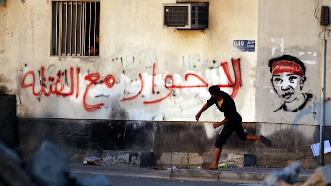 """A woman and her child watch clashes between anti-government protesters and riot police from their window as a protester hurls a stone toward police in Sitra, Bahrain, on Wednesday, Feb. 13, 2013. Clashes erupted in several opposition villages around the kingdom on the eve of the second anniversary of a pro-democracy uprising. Graffiti on the wall reads: """"No to dialogue with murderers."""" (AP Photo/Hasan Jamali)"""
