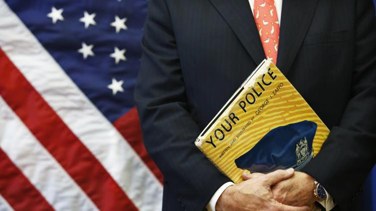 Bratton holds a book as he attends a news conference in Brooklyn