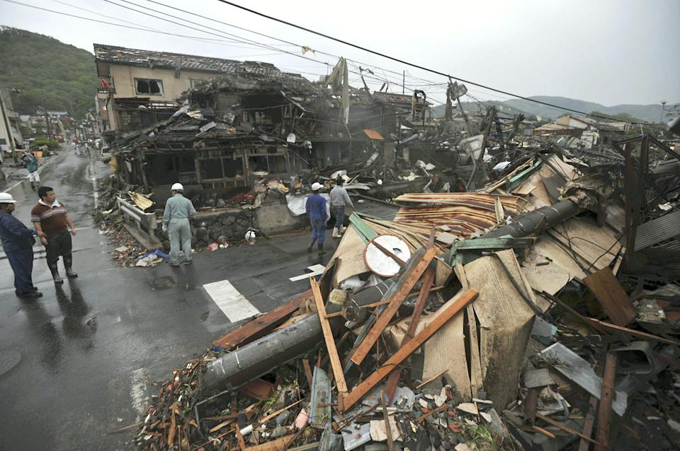 People look at damaged buildings after a tornado struck Tsukuba city, northeast of Tokyo, Sunday, May 6, 2012. The tornado tore through the area, injuring at least 30 people, destroying dozens of homes and leaving thousands more without electricity. (AP Photo/Yomiuri Shimbun, Tetsu Joko) JAPAN OUT