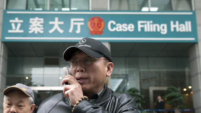 In this photo taken Thursday, Nov. 29, 2012, Li Zhuang, an ex-lawyer who claims he was framed and wrongfully jailed for 18 months, talks on his mobile phone in front of the Chongqing No. 1 Intermediate People's Court in southwest China's Chongqing Municipality.  With China's new leaders freshly installed in power, authorities are turning their attention to tying up loose ends in the sprawling, scandal-ridden city once ruled by populist politician Bo Xilai before his downfall buffeted the leadership transition. In the past two weeks, authorities in Chongqing released Li, a lawyer disbarred after being convicted of having one of his clients lie in court, as well as a village official who had been sent to a labor camp for criticizing Bo. (AP Photo) CHINA OUT