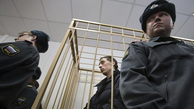 "Bolshoi soloist Pavel Dmitrichenko, center, listens in a courtroom in Moscow, Russia, Thursday, March 7, 2013. The star dancer accused of masterminding the attack on the Bolshoi ballet chief acknowledged Thursday that he gave the go-ahead for the attack, but said he did not order anyone to throw acid on the artistic director's face.Dmitrichenko told a Moscow court that he had complained about ballet chief Sergei Filin to an acquaintance, who offered to ""beat him up."" (AP Photo/Alexander Zemlianichenko)"