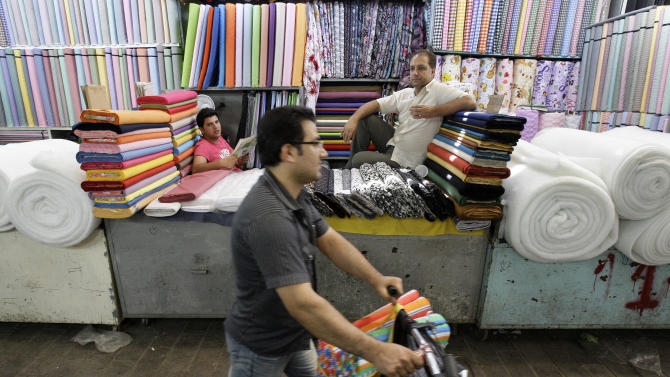 In this picture taken on Saturday, July 14, 2012, an Iranian man with a bike walks at the main bazaar, in Tehran, Iran, as two textile merchants wait for customers. Police threatened merchants who closed their shops in Tehran's main bazaar and launched crackdowns on sidewalk money changers on Wednesday as part of a push to halt the plunge of Iran's currency, which has shed more than a third its value in less than a week.(AP Photo/Vahid Salemi)