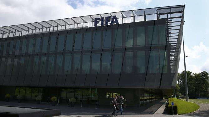 Members of the media walk in front of the headquarters of soccer's international governing body FIFA in Zurich