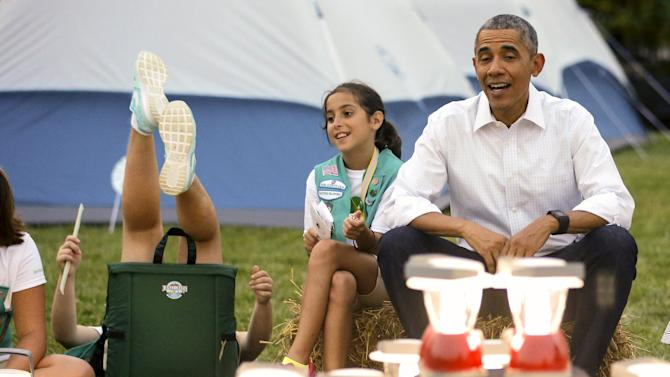 A Girl Scout loses her balance in her camp chair around pretend campfire as Obama and the first lady welcome scouts to camp-out on South Lawn of White House in Washington