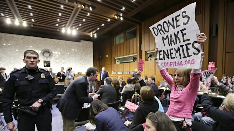 CODEPINK co-founder Medea Benjamin, right and other CODEPINK protestors,  a group opposed to U.S. militarism, disrupt the start of the Senate Intelligence Committee confirmation hearing for John Brennan, Thursday, Feb. 7, 2013, on Capitol Hill in Washington. (AP Photo/J. Scott Applewhite)