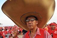 A &quot;Red Shirt&quot; supporter of Thailand&#39;s fugitive former premier Thaksin Shinawatra at a rally in Siem Reap province, Cambodia, on Saturday. Thaksin told the rally Thailand can begin to heal its deep political rifts